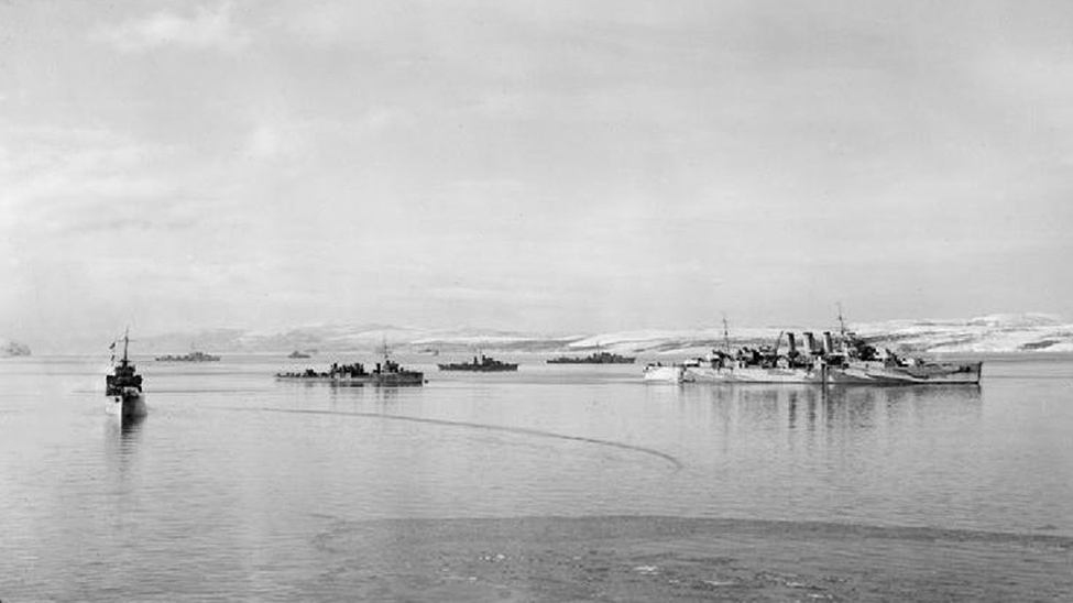 HMS NORFOLK with destroyers and merchant ship whilst on northern convoy duty.