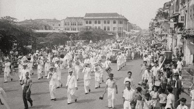 A brass band leads a procession of the people of Singapore in a celebratory parade to mark the end of Japanese rule.