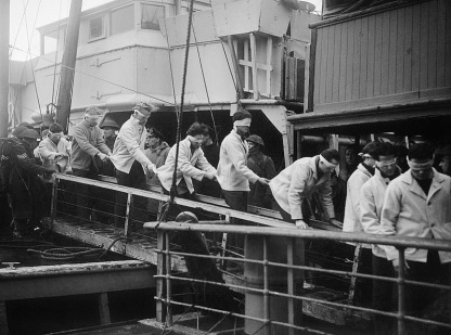 Scharnhorst Survivors at Scapa Flow, 2 January 1944 Blindfolded SCHARNHORST survivors, in merchant seaman rescue kit, walking down a gang-plank on their way to internment.